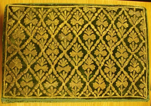 The Qur'an is bound in green velvet, worked with silver thread