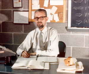 A bearded man wearing spectacles, a shirt and a tie sits at a desk covered with papers. Part of a blackboard and a notice board are visible on the wall behind him.