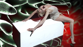 A blonde woman in a white leotard contorts herself in apparent pain on a hospital bed, on a background of microscope images of cells.