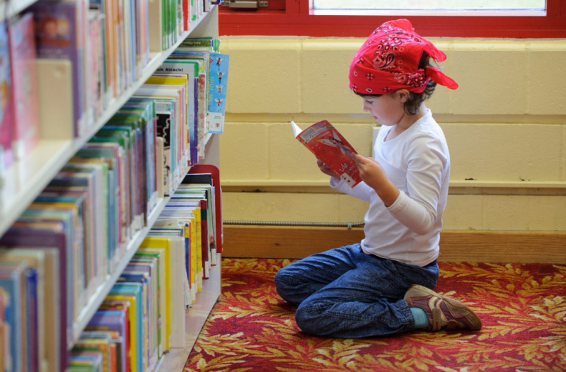 Young girl in a red bandana reading in front of a bookcase.