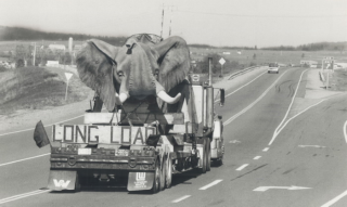 A black and white photo of a sculpture of an elephant being carried on a truck bed on a highway.