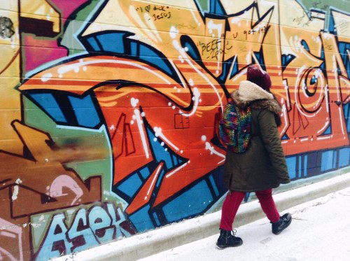 photo of girl passing graffiti in Kensington Market