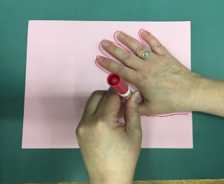 One hand tracing the outline of another on to a piece of paper.