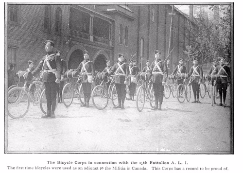Men in military uniforms with rifles assemble standing beside bicycles