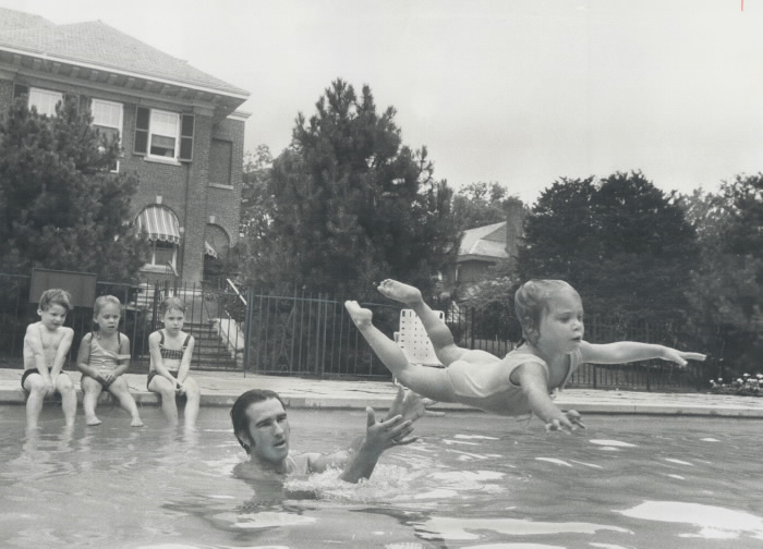 A swimming instructor standing in a pool throws a young child into the water.