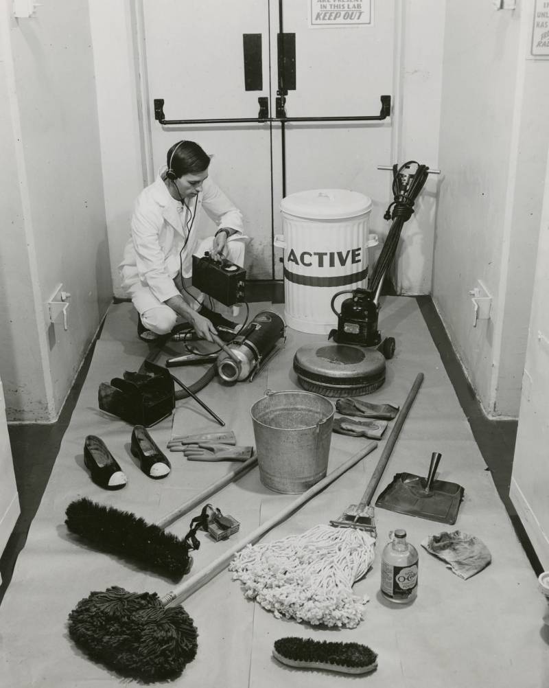 Man using a Geiger counter to measure radioactivity of various items